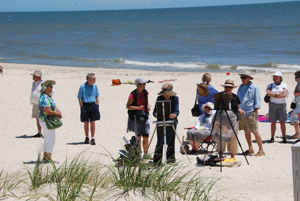 People gather on the St. George Island beach to watch artist Nancy Mertz create one of her fabulous pastel paintings of the lighthouse there.