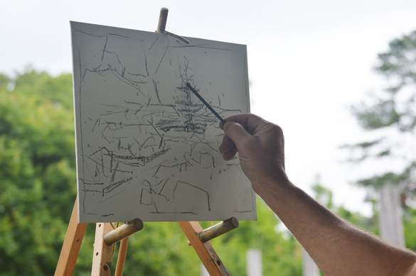 Sketching in his basic composition lines with vine charcoal.